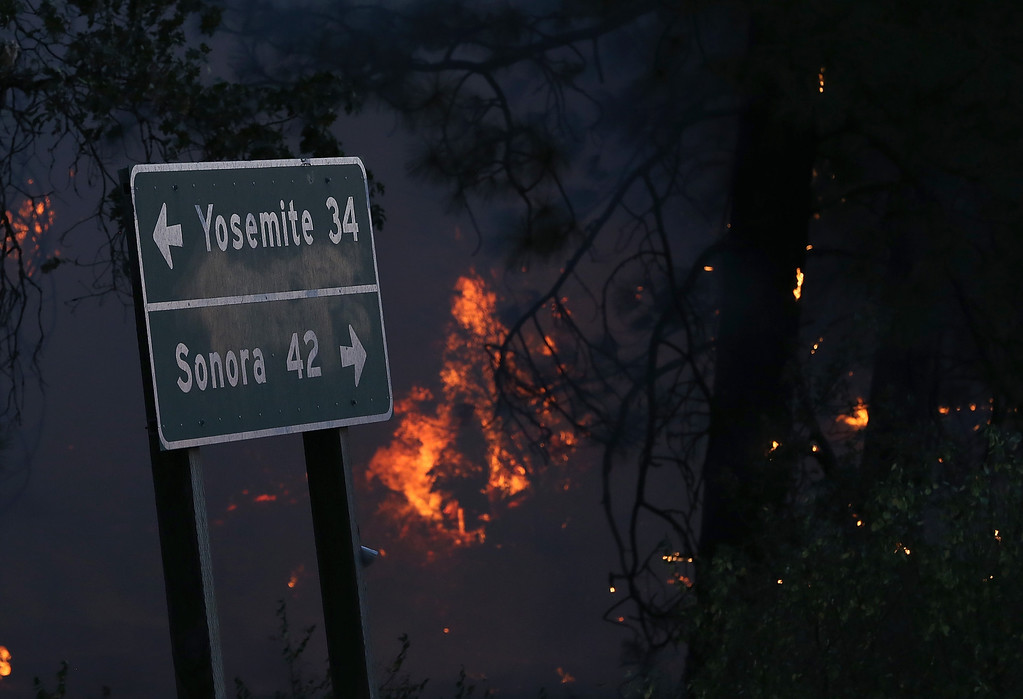 . GROVELAND, CA - AUGUST 21:  Flames from the Rim Fire burn near a road sign pointing towards Yosemite on August 21, 2013 in Groveland, California. The Rim Fire continues to burn out of control and threatens 2,500 homes outside of Yosemite National Park. Over 400 firefighters are battling the blaze that is only 5 percent contained.  (Photo by Justin Sullivan/Getty Images)