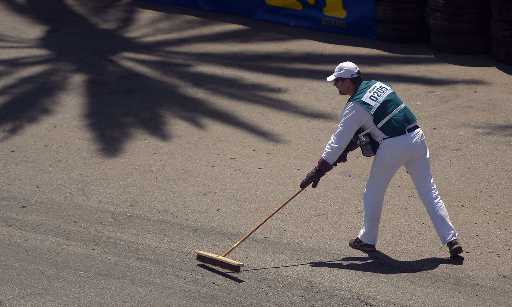 . During a break in the action, a corner worker sweeps debris from the driving line in Long Beach, CA on Friday, April 17, 2015. The 40th annual Toyota Grand Prix of Long Beach kicked off with practices for all of the racing divisions. (Photo by Scott Varley, Daily Breeze)