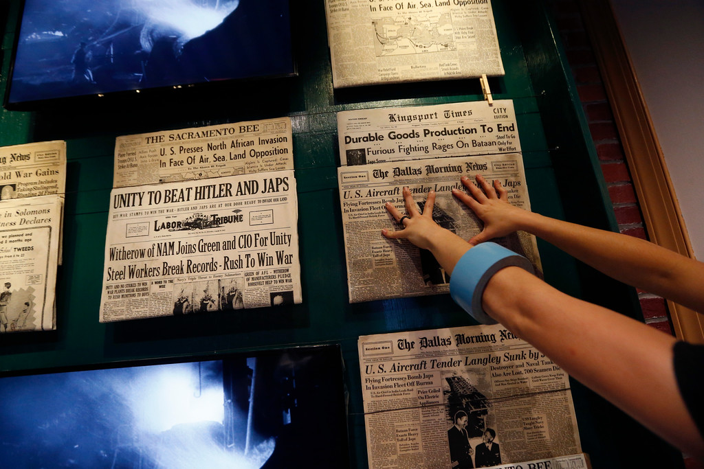". Kristin Guillot works on installing images of newspapers as part of the permanent exhibit ""Salute to the Home Front\"" at the National World War II Museum which will open to the public this Saturday, in New Orleans, Monday, June 5, 2017. The exhibit tells the home front story from the 1920s to the development of the atomic bomb. (AP Photo/Gerald Herbert)"
