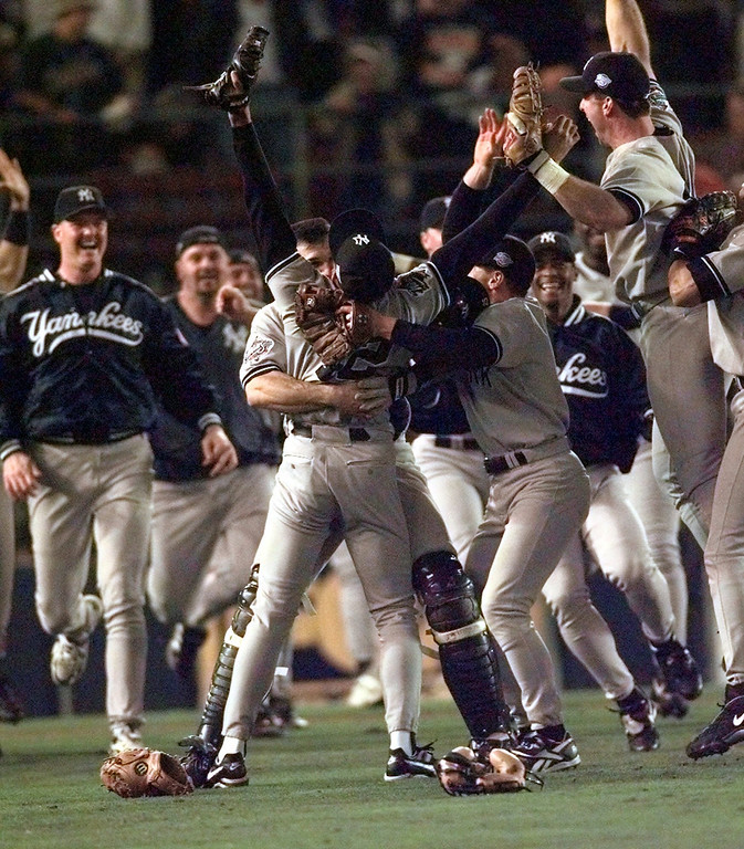 . In this Oct. 21, 1998 file photo, New York Yankees pitcher Mariano Rivera raises both arms as he\'s hugged by catcher Joe Girardi after the Yankees defeated the San Diego Padres to win the World Series, in San Diego. (AP Photo/Lenny Ignelzi, File)