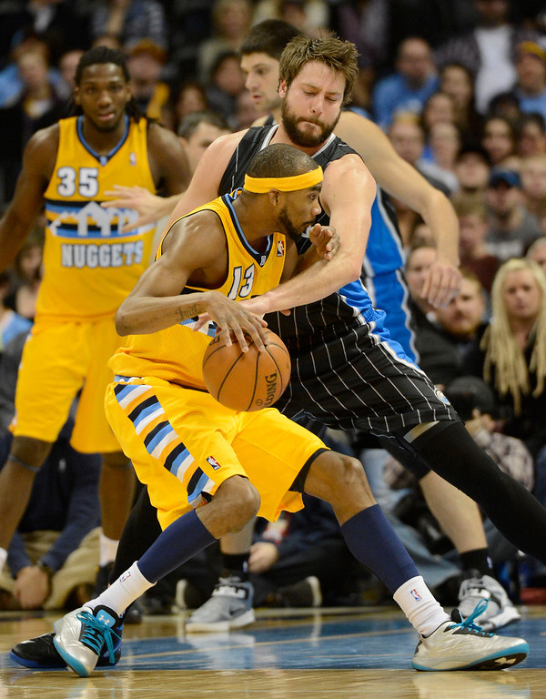 . Orlando Magic power forward Josh McRoberts (17) reaches in on Denver Nuggets small forward Corey Brewer (13) to knock the ball away during the fourth quarter Wednesday, January 9, 2013 at Pepsi Center. John Leyba, The Denver Post