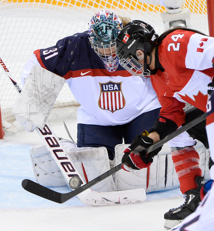 . Canada\'s Natalie Spooner shoots on US goalkeeper Jessie Vetter during the Women\'s Ice Hockey Group A match Canada vs USA at the Shayba Arena during the Sochi Winter Olympics on February 12, 2014. AFP PHOTO / JONATHAN NACKSTRAND/AFP/Getty Images