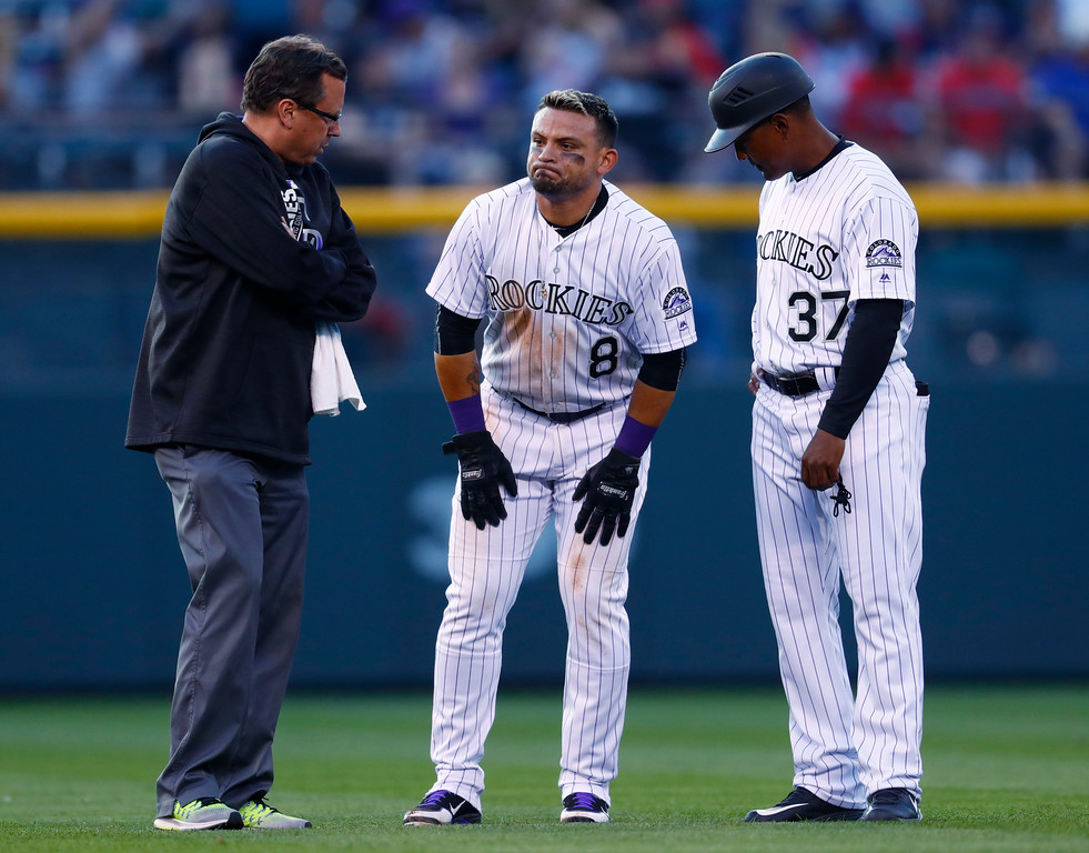 . Colorado Rockies assistant athletic trainer Scott Gehret, left, and first base coach Tony Diaz, right, look on as Gerardo Parra reacts after hurting his leg while trying to steal second base against the Cleveland Indians in the third inning of an interleague baseball game Tuesday, June 6, 2017, in Denver. Parra was forced to leave the game which the Rockies won 11-3. (AP Photo/David Zalubowski)
