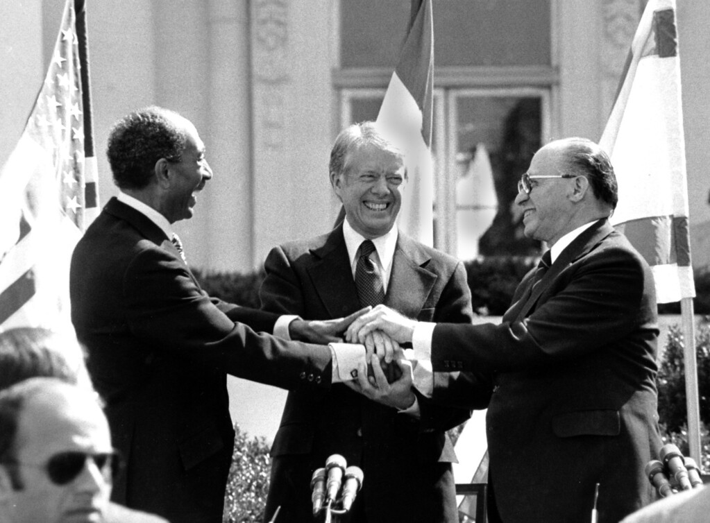 . Egyptian President Anwar Sadat, left, U.S. President Jimmy Carter, center,  and Israeli Prime Minister Menachem Begin clasp hands on the north lawn of the White House after signing the peace treaty between Egypt and Israel on March 26, 1979. Sadat and Begin were awarded the Nobel Peace Prize for accomplishing peace negotiations in 1978. The rest of the Arab world shunned Sadat, condemning his initiative for peace. President Carter was pivotol for the two leaders to meet at Camp David and as a result, peace began between Arabs and Jews. (AP Photo/ Bob Daugherty)