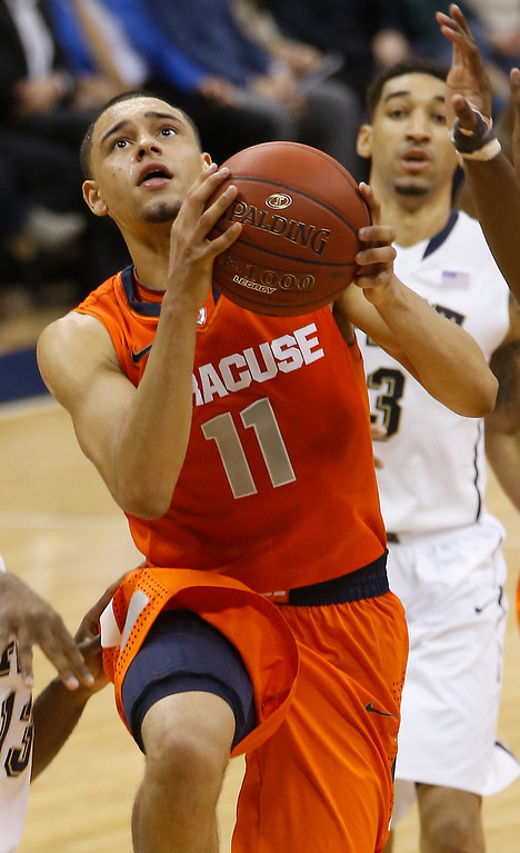 . Syracuse\'s Tyler Ennis (11) shoots in front of Pittsburgh\'s Cameron Wright during the second half of an NCAA college basketball game on Wednesday, Feb. 12, 2014, in Pittsburgh. (AP Photo/Keith Srakocic)
