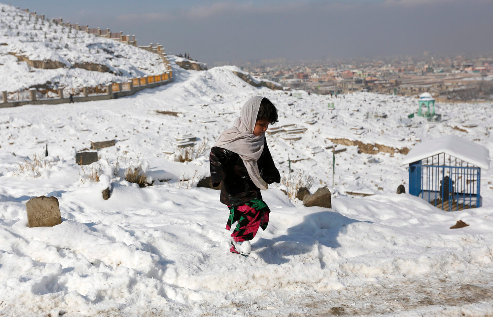 Description of . A girl walks in a snow-covered cemetery in Kabul December 18, 2012. REUTERS/Mohammad Ismail