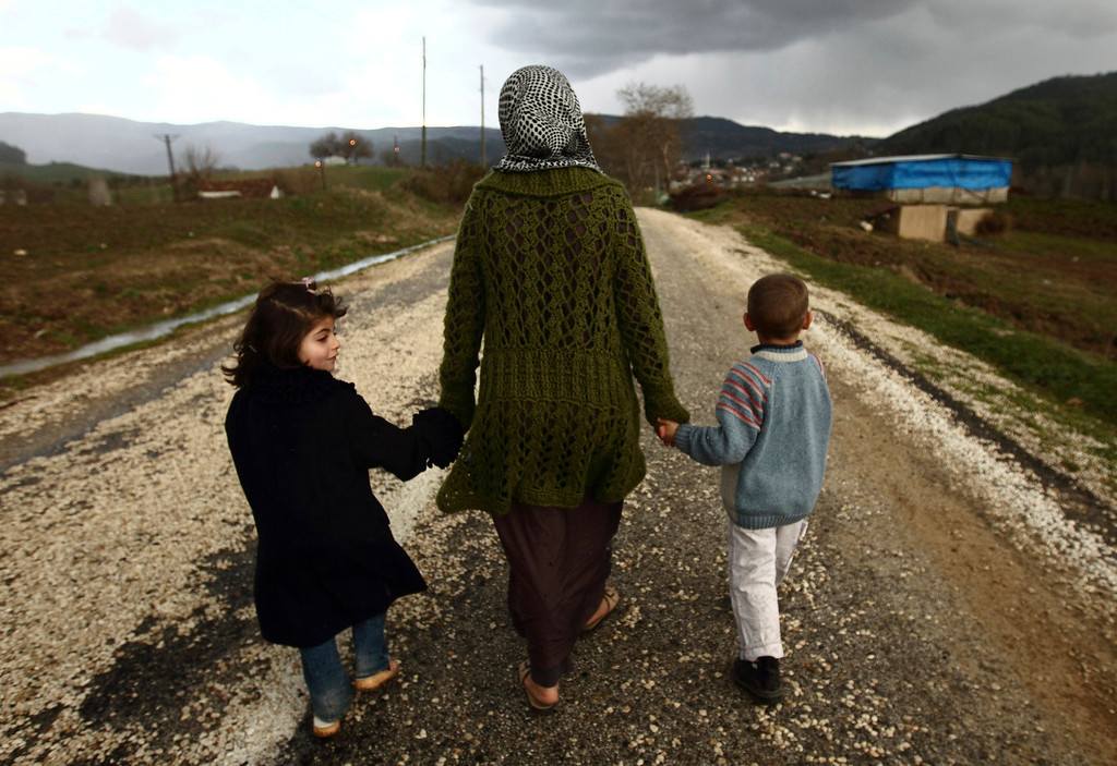 . Sawssan  Abdelwahab, who fled Idlib in Syria, walks with her children outside the refugees camp near the Turkish-Syrian border in the southeastern city of Yayladagi February 16, 2012. REUTERS/Zohra Bensemra