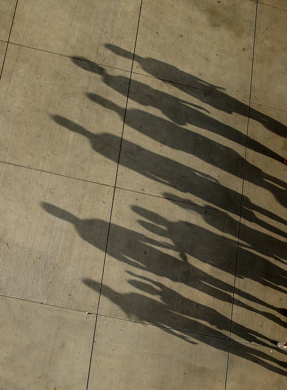. Fans cast long shadows as they walk into Kauffman Stadium before a baseball game between the Kansas City Royals and the Cleveland Indians on Tuesday, July 3, 2018, in Kansas City, Mo. (AP Photo/Charlie Riedel)