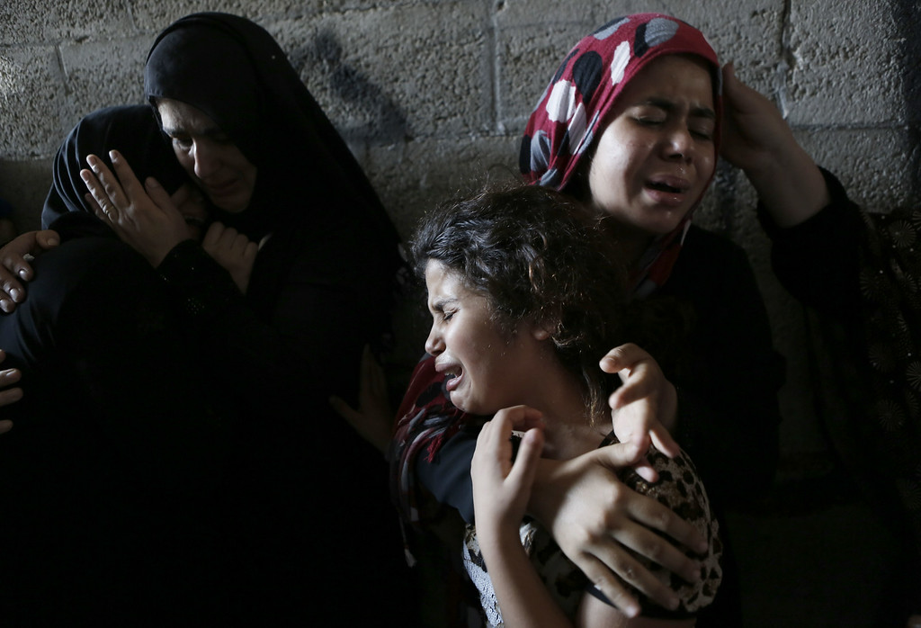 . The daughters (R) of Hasan Baker, 60-years-old, grieve during his funeral in Gaza City, on July 22, 2014. A series of Israeli air strikes early killed seven people in Gaza, including five members of the same family, emergency services spokesman Ashraf al-Qudra said. The deaths hike the total Palestinian toll to 583 since the Israeli military launched Operation Protective Edge on July 8 in a bid to stamp out rocket fire from Gaza. AFP PHOTO / MOHAMMED ABED/AFP/Getty Images