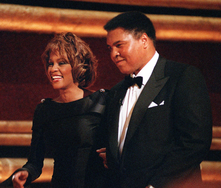 ". Former World Heavyweight Boxing Champion Muhammad Ali is greeted by singer Whitney Houston as he arrives on stage at New York\'s Radio City Music Hall to accept a GQ ""Men of the Year\"" Award Wednesday, Oct. 21, 1998.   (AP Photo/Mitch Jacobson)"