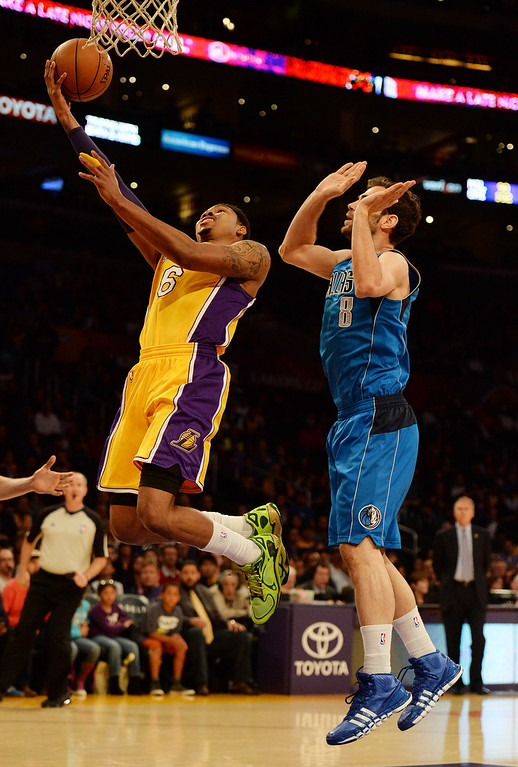 . Los Angeles Lakers guard Kent Bazemore (6) drives to the basket past Dallas Mavericks guard Jose Calderon (8) in the first quarter during an NBA basketball game in Los Angeles, Calif., on Friday, April 4, 2014.  (Keith Birmingham Pasadena Star-News)