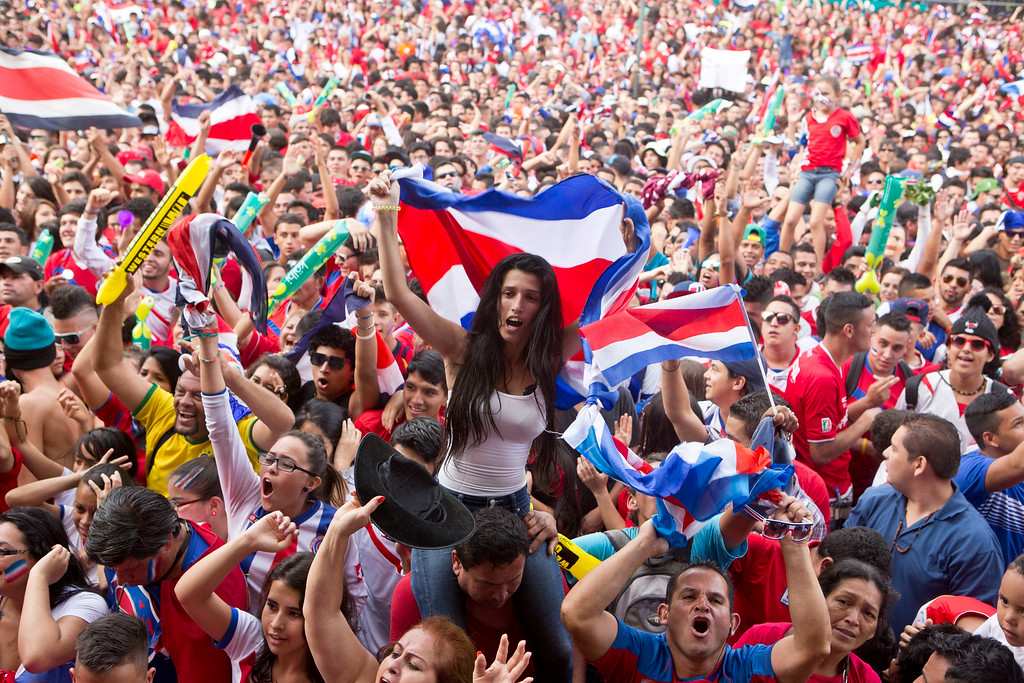 . Costa Rica soccer fans celebrate a goal against Greece as they watch the World Cup round of 16 match on TV set up in a public square in San Jose, Costa Rica, Sunday, June 29, 2014. (AP Photo/Esteban Felix)