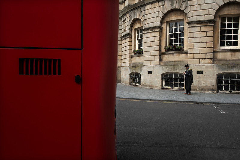Red double decker bus with a university student in the background.  Bath, England, 2018