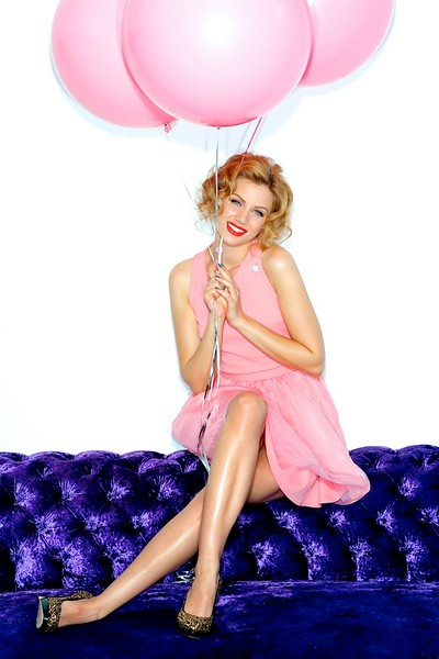Beautiful blonde in a party dress holding pink balloons