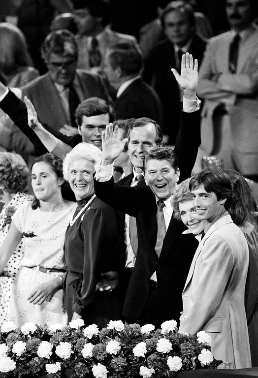 . With family members at their sides, Ronald Reagan and running mate George Bush wave to the cheering throng in Detroit on July 17, 1980, as the 1980 Republican Convention comes to a close. From left: Bush\'s daughter Dorothy, his wife, Barbara; Bush; Reagan; Nancy Reagan; and Reagan son Ron. (AP Photo)