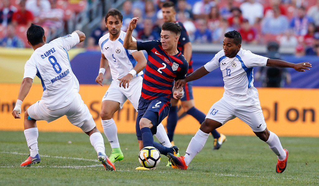 . United States\' Jorge Villafana (2) works through Nicaragua\'s Marlon Lopez (8), Daniel Candena (9) and Bryan Garcia (13) during a CONCACAF Gold Cup soccer match in Cleveland, Ohio, Saturday, July 15, 2017. (AP Photo/Ron Schwane)
