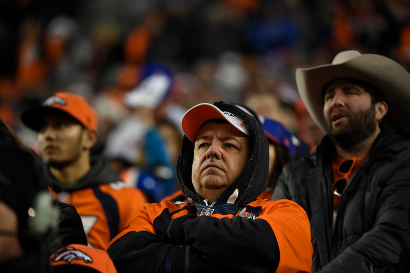 . Broncos fans sit dejected in the fourth quarter. The Denver Broncos played the Indianapolis Colts in an AFC divisional playoff game at Sports Authority Field at Mile High in Denver on January 11, 2015. (Photo by Joe Amon/The Denver Post)