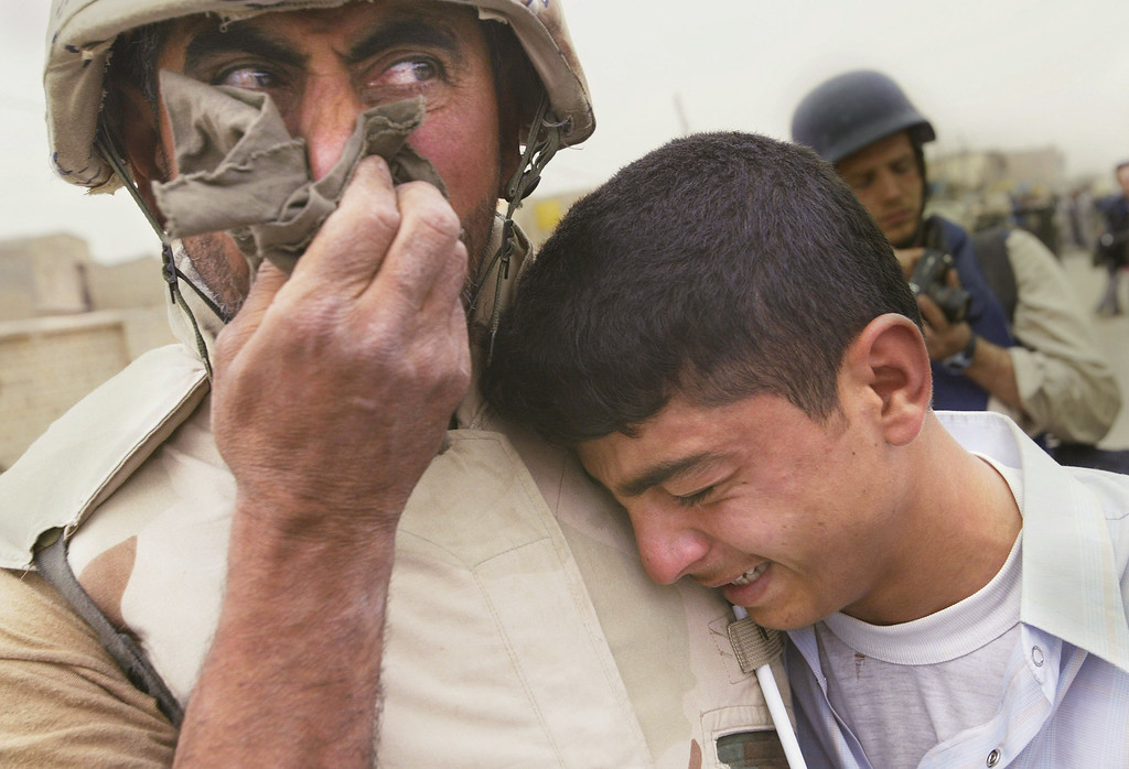 . Khudair Al-Amiri (L) cries with his son, Ali Al-Amiri, as they are reunited after the father\'s return to his hometown as a translator for American Marines April 7, 2003 in Qal\'at Sukkar, Iraq. Al-Amiri fled Iraq after the first Gulf war and returned with the 24th Marine Expeditionary Unit, seeing members of his family and village for the first time in over a decade. (Photo by Chris Hondros/Getty Images)
