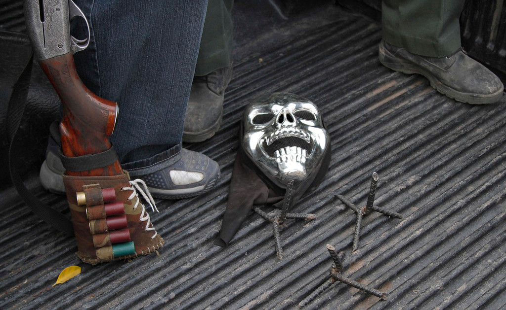. In this May 19, 2013 photo, a mask and spikes for puncturing tires lay next to the feet of armed men from a local self-defense group as they ride in a pick-up truck near the town of La Ruana, Mexico. Self-defense groups started to spring up in February to fight back the Knights Templar drug cartel which is extorting protection payments from cattlemen and lime growers, butchers and even marijuana growers. The federal government sees both the self-defense forces and the cartel as dangerous enemies. (AP Photo/Marco Ugarte)