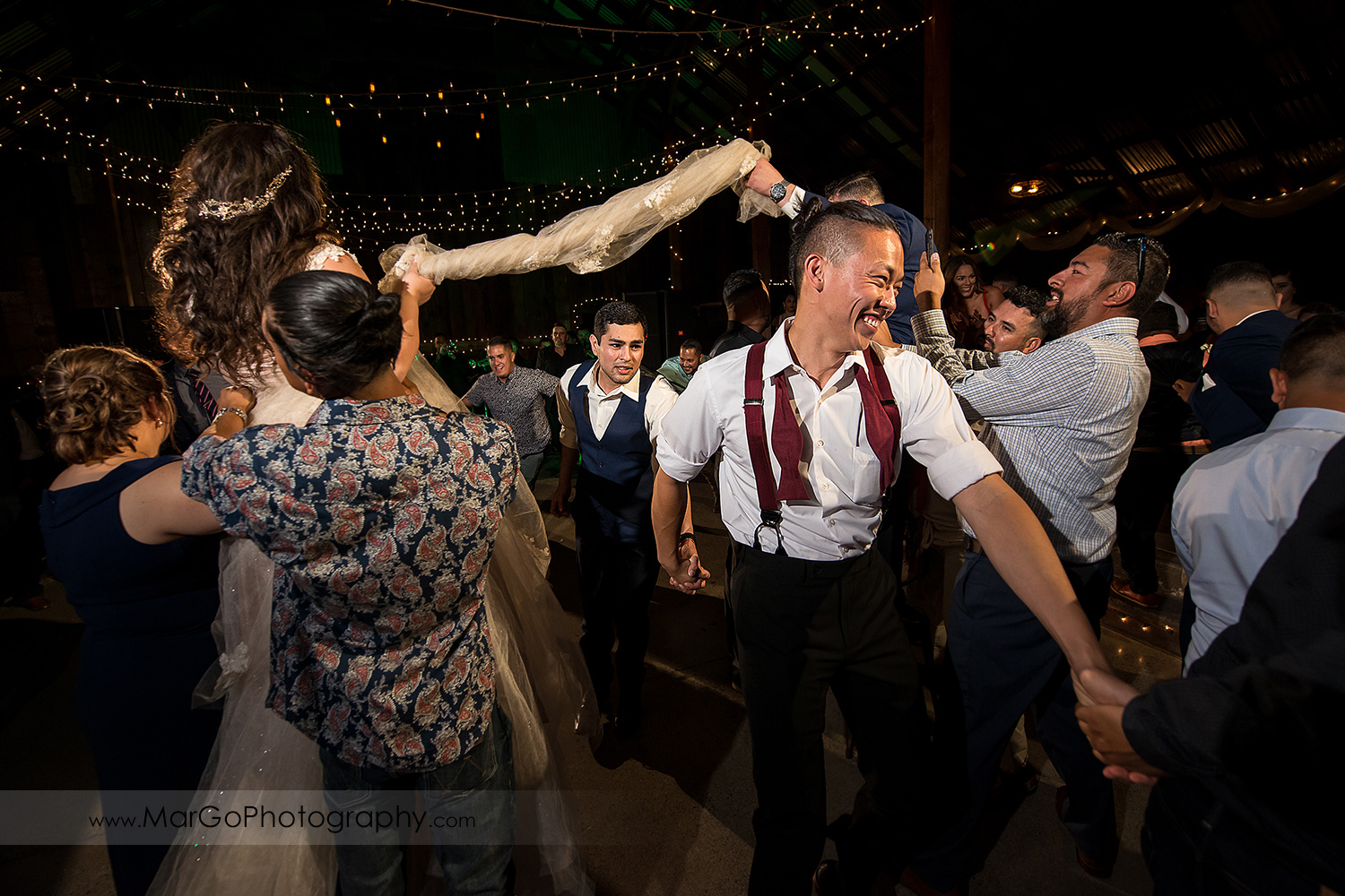 bride and groom standing on chairs during La Vibora de La Mar - the Sea Snake dance with male part of wedding guests at Taber Ranch Vineyards