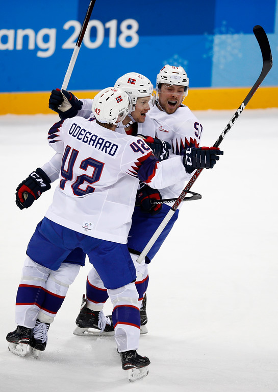 . Henrik Odegaard (42), Alexander Bonsaksen (47) and Olsen Mats Rosseli (51), of Norway, celebrate after defeating Slovenia in the qualification round of the men\'s hockey game in overtime at the 2018 Winter Olympics in Gangneung, South Korea, Tuesday, Feb. 20, 2018. Norway won 2-1. (AP Photo/Jae C. Hong)