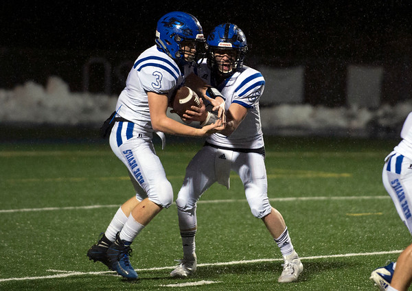 12/09/19 Wesley Bunnell | StaffrrPlainville football was defeated by Bloomfield in a CIAC playoff game on a rainy Monday night at Bloomfield High School. QB Christian Collin (6) hands off to RB Beau Lasher (3).