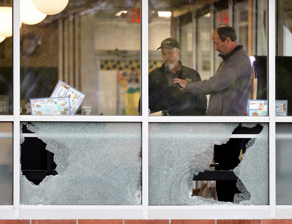 . People look over an area near a window shot out at a Waffle House restaurant Sunday, April 22, 2018, in Nashville, Tenn. Several people died after a gunman opened fire at the restaurant early Sunday. (AP Photo/Mark Humphrey)