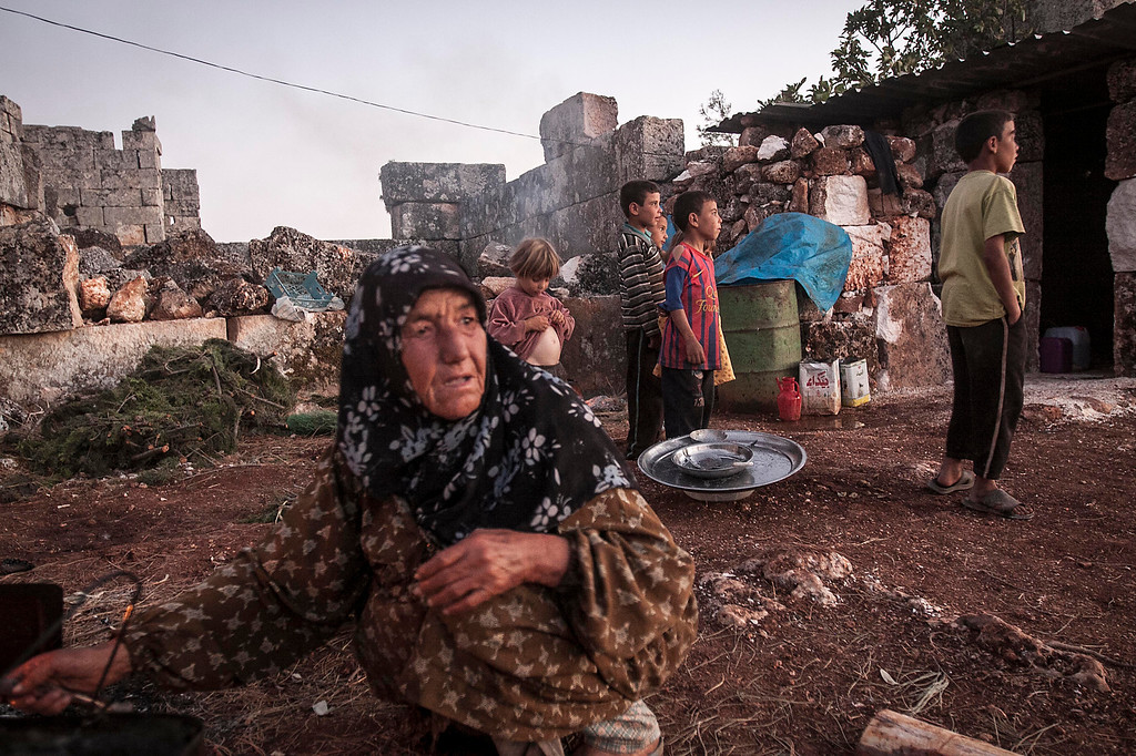 . In this Thursday, Sept. 26, 2013 photo, a displaced Syrian woman cooks a meal for dinner as children play in the sunset near Kafer Rouma, in ancient ruins used as temporary shelter by those families who have fled from the heavy fighting and shelling in the Idlib province countryside of Syria. The families moved their property from their old houses in their villages to the new ones amid the ruins.  What they could carry has been brought with them _ pots and pans, stoves, torches, plastic tarps.(AP Photo)