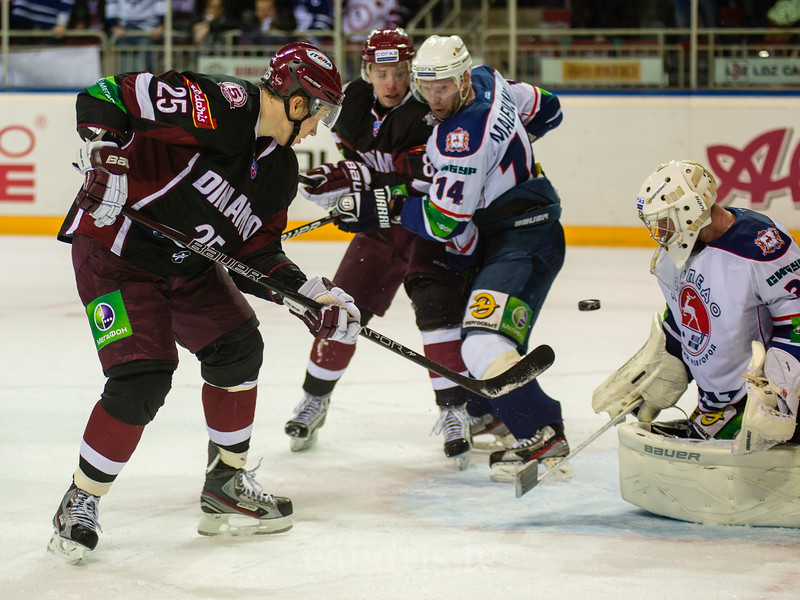 Andris Dzerins (25) and Koval Vitaly (31) watch the puck
