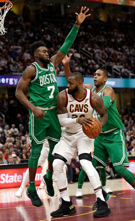 . Cleveland Cavaliers\' LeBron James (23) tries to get past Boston Celtics\' Jaylen Brown (7) and Al Horford (42) in the second half of an NBA basketball game, Tuesday, Oct. 17, 2017, in Cleveland. (AP Photo/Tony Dejak)