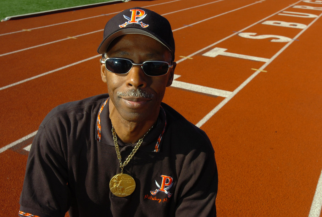 . Eddie Hart, wearing the gold medal he won in the 4x100 relay at the 1972 Olympics, poses for a photo on the track where it all began at Pittsburg High School in Pittsburg, Calif. on Dec. 9, 2005. (Kristopher Skinner/Bay Area News Group Archives)