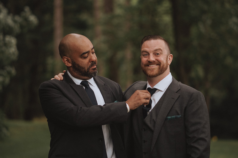 A groomsman makes a funny face as he straightens the tie of the grinning groom.