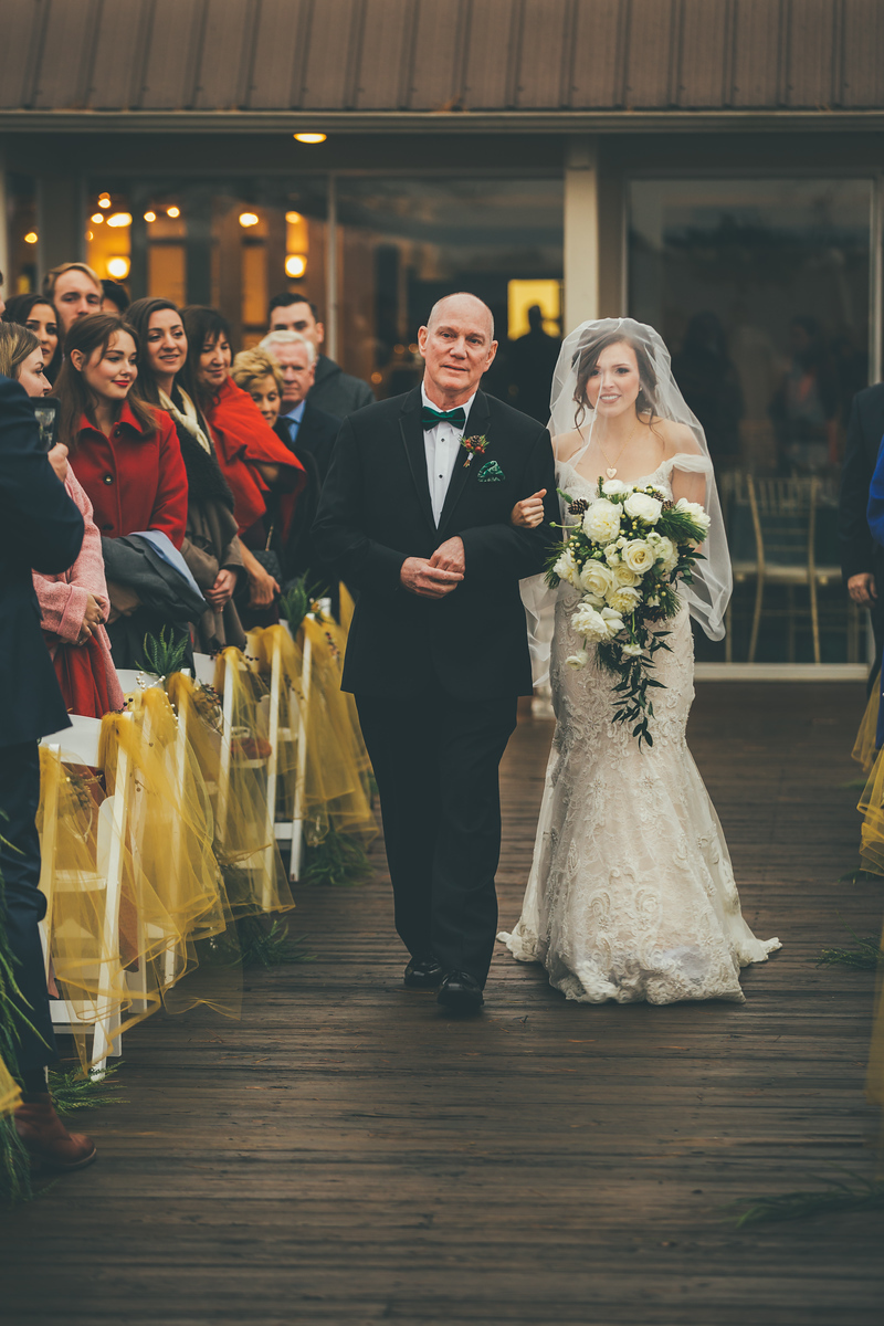 a father walking his daughter down the weddine asile lined with gold and green accents