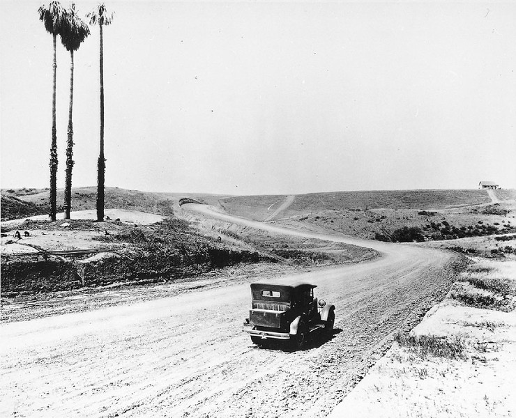 Automobile driving down Sunset Boulevard during the road's construction, ca.1925