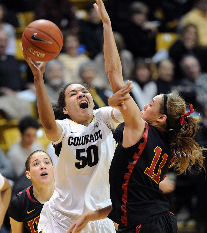 . Jamee Swan of Colorado drives into Cassie Harberts of USC   during the first half of the March 2, 2014 game in Boulder, Colo. (Class Grassmick/Daily Camera)