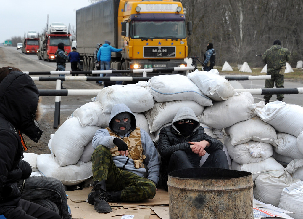 . Masked men who called themselves members of local militia rest at their checkpoint on a highway that connect Black Sea Crimea  peninsula to mainland Ukraine near the city of Armyansk, on February 28, 2014.  AFP PHOTO / VIKTOR DRACHEV/AFP/Getty Images