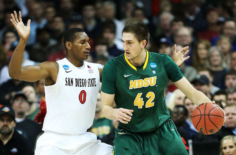 . Marshall Bjorklund #42 of the North Dakota State Bison drives against Skylar Spencer #0 of the San Diego State Aztecs in the first half during the Third Round of the 2014 NCAA Basketball Tournament at Spokane Veterans Memorial Arena on March 22, 2014 in Spokane, Washington.  (Photo by Stephen Dunn/Getty Images)