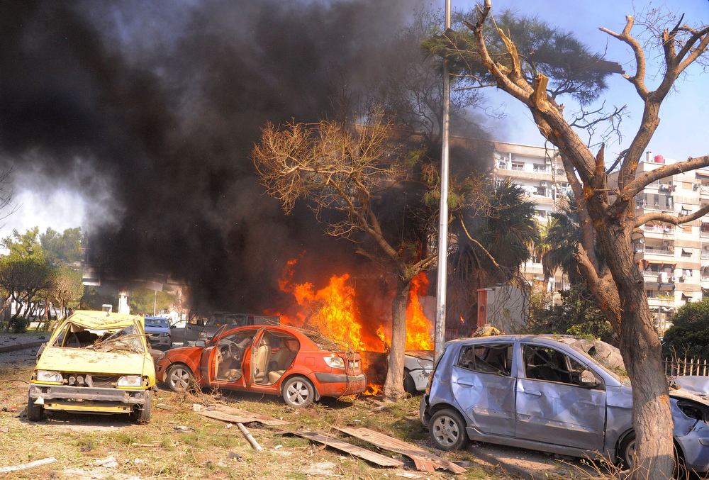 Description of . This photo released by the Syrian official news agency SANA, shows flames and smoke rising from burned cars after a huge explosion that shook central Damascus, Syria, Thursday, Feb. 21, 2013. A car bomb shook central Damascus on Thursday, exploding near the headquarters of the ruling Baath party and the Russian Embassy, eyewitnesses and opposition activists said. (AP Photo/SANA)
