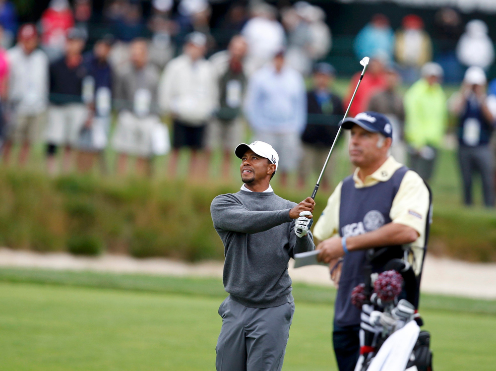 . Tiger Woods (L) of the U.S. hits from the 16th fairway as Steve Williams, caddie for Australia\'s Adam Scott and Woods\' former caddie, looks on during the weather delayed first round of the 2013 U.S. Open golf championship at the Merion Golf Club in Ardmore, Pennsylvania, June 14, 2013. REUTERS/Matt Sullivan