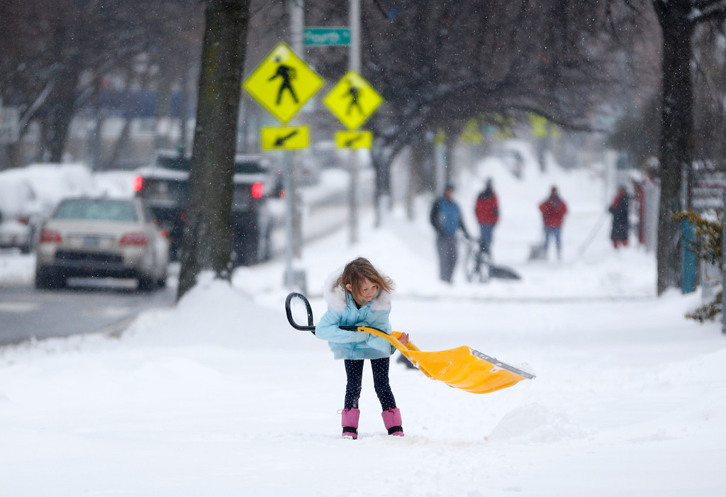 . A young girl plays with a shovel following an overnight snowstorm, Tuesday, Jan. 27, 2015, in Jersey City, N.J.  A storm packing blizzard conditions spun up the East Coast early Tuesday, pounding coastal eastern Long Island into Maine with high winds and heavy snow.(AP Photo/Julio Cortez)