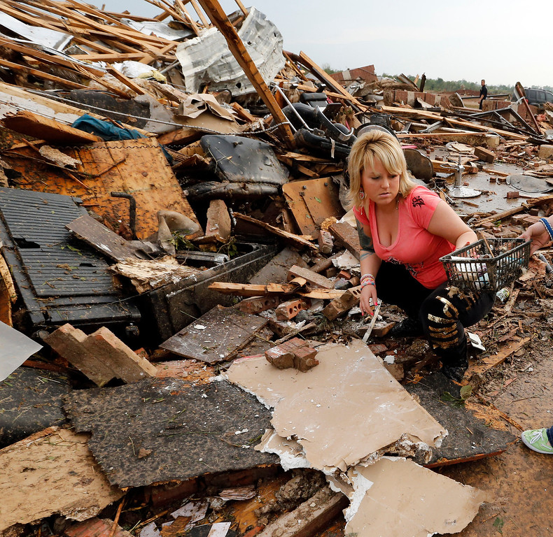 . Sydney Whittaker salvages items from Trends Salon on Monday, May 20, 2013 in Moore, Okla. A monstrous tornado roared through the Oklahoma City suburbs, flattening entire neighborhoods with winds up to 200 mph, setting buildings on fire and landing a direct blow on an elementary school. (AP Photo/The Oklahoman, Steve Sisney)