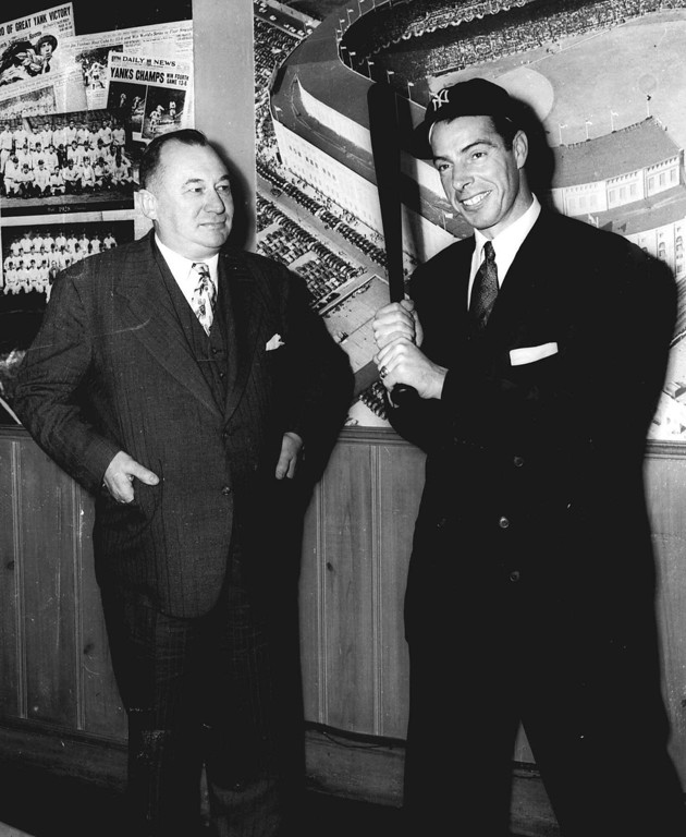 . New York Yankees center fielder Joe DiMaggio, right, wears his cap and brandishes his bat as Yankees general manager George Weiss looks on at the teams New York offices, after DiMaggio signed his 1950 contract which was worth about $100,000, Jan. 24, 1950.  (AP Photo)