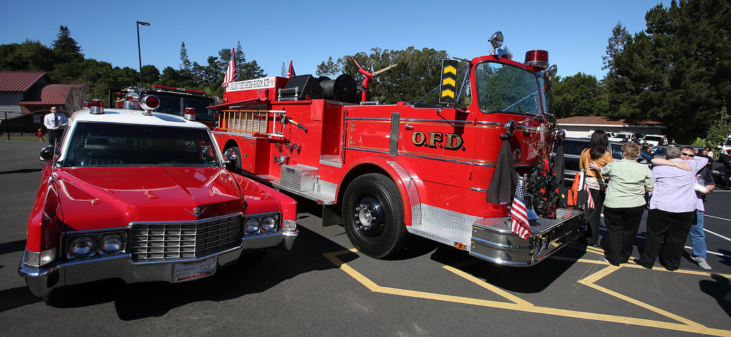 . Mourners console each other near an old Oakland fire truck and ambulance during funeral services for Santa Clara paramedic Quinn Boyer, 34, of Dublin, at St. Theresa Catholic Church in Oakland, Calif., on Tuesday, April 16, 2013.  (Jane Tyska/Staff)