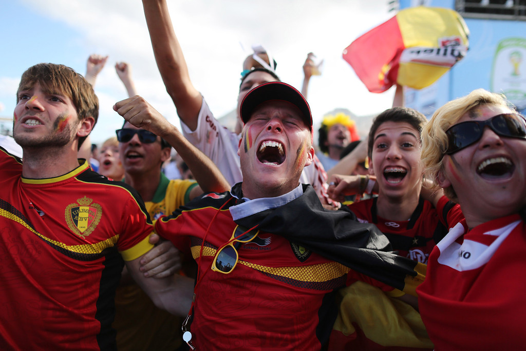 . Soccer fans celebrate the goal scored by Belgium as they watch a live broadcast of the group H World Cup match between Belgium and Russia inside the FIFA Fan Fest area on Copacabana beach, in Rio de Janeiro, Brazil, Sunday, June 22, 2014. (AP Photo/Leo Correa)