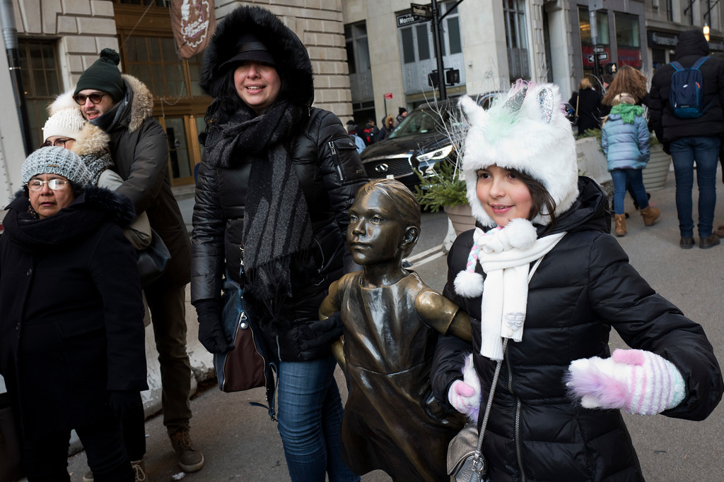 . A young girl is all bundled up as she poses with the Fearless Girl statue in lower Manhattan, Wednesday, Dec. 27, 2017, in New York. A white Christmas for much of the Northeast and Midwest has given way to bitter cold until the New Year. (AP Photo/Mark Lennihan)