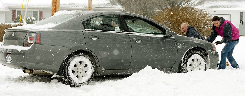 . Maribeth Joeright/MJoeright@News-Herald.com Tom and Dana Husa attempt to push Julie Smith\'s car out of her driveway on Wilson Drive in Mentor, Wednesday. After their attempt failed, the Husa\'s, who run a plowing service and just happened to be passing by, chained Smith\'s car to their truck and freed the vehicle from the snowy driveway. The couple ended up getting some extra business when Smith paid them to plow her driveway.