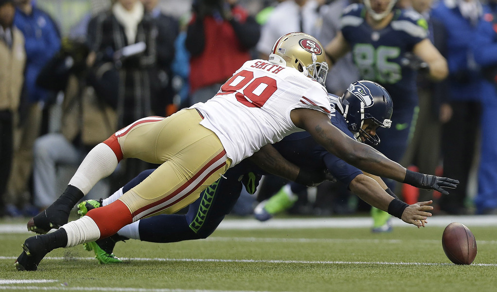 . Seattle Seahawks\' Russell Wilson and San Francisco 49ers\' Aldon Smith go after Wilson\'s fumble on the first play of the first half of the NFL football NFC Championship game Sunday, Jan. 19, 2014, in Seattle. The 49ers recovered the ball. (AP Photo/Marcio Jose Sanchez)