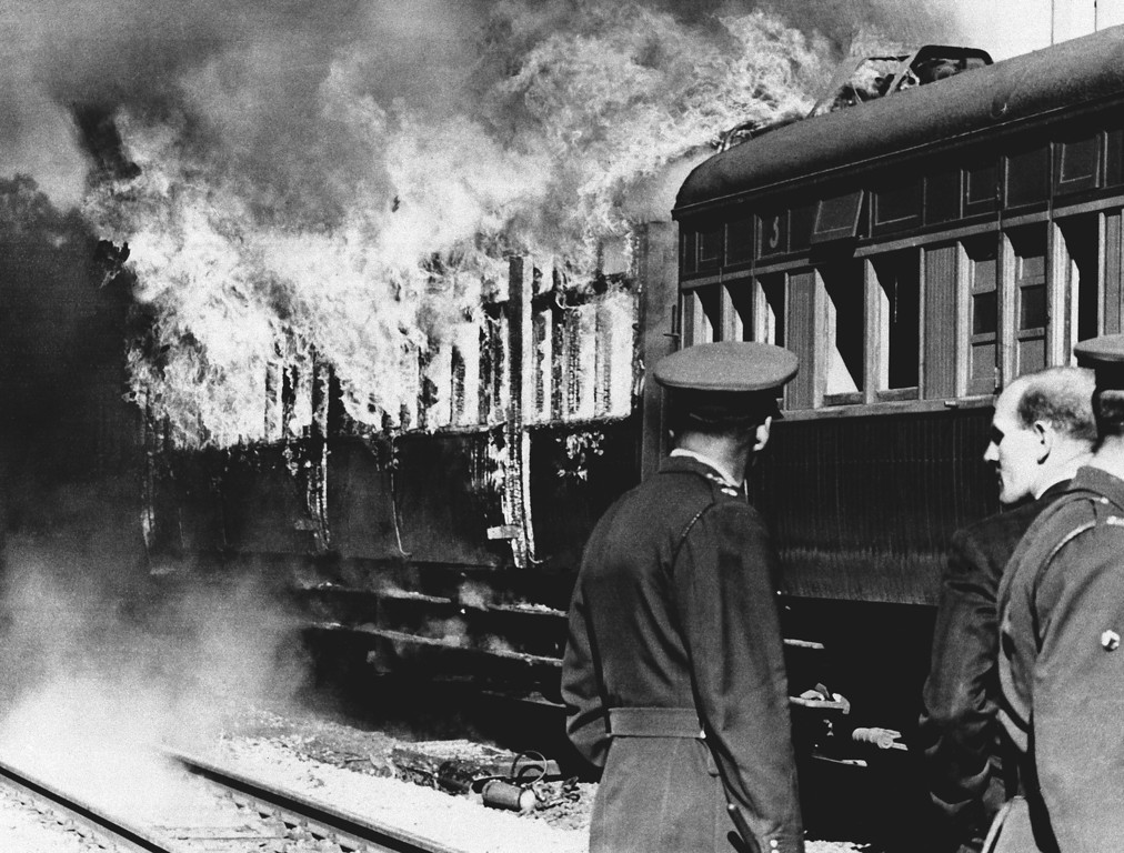 . South African police stand by blazing railway coaches set on fire by Africans after a train crash on the outskirts of Johannesburg, South Africa on August 1, 1966. Police reported five Africans in the crowded train were killed and 248 injured. The irate passengers stoned the white train crewmen, seriously injuring them, and set fire to some coaches. (AP Photo)