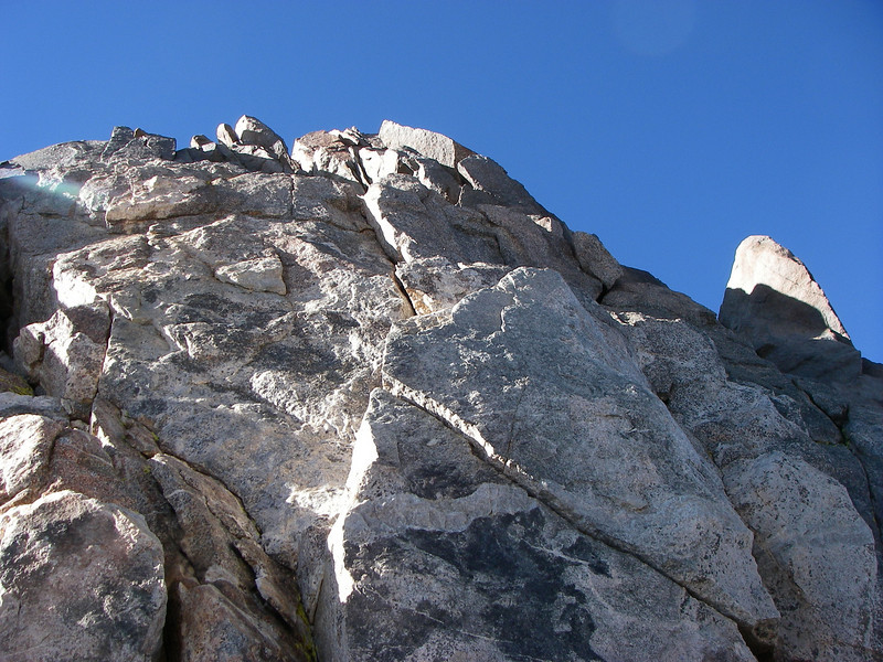 The first ascent party on August 13, 1933, included Bestor Robinson, Lewis F. Clark, Glen Dawson, Jules Eichorn, Francis Farquhar, Robert L. M. Underhill, and Norman Clyde. However, not all of them made it to the top of the summit monolith, due to an approaching storm. Dawson and Eichorn made it