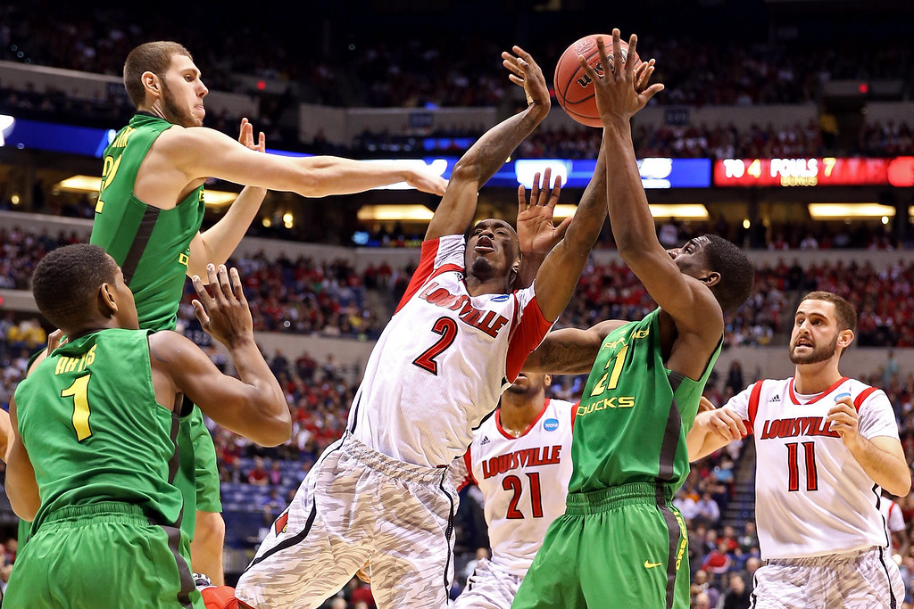 . Russ Smith #2 of the Louisville Cardinals loses the ball as he drives to the basket in the first half against Dominic Artis #1, Ben Carter #32 and Damyean Dotson #21 of the Oregon Ducks during the Midwest Region Semifinal round of the 2013 NCAA Men\'s Basketball Tournament at Lucas Oil Stadium on March 29, 2013 in Indianapolis, Indiana.  (Photo by Andy Lyons/Getty Images)